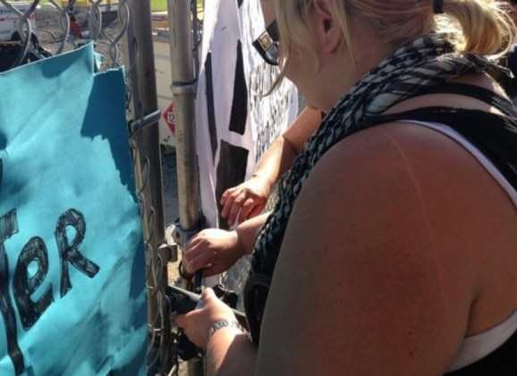 Trish Mills of Occupy Toronto illegally putting a lock on the front gate...