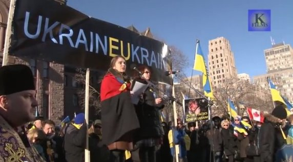 Ukrainian Insurgent Army flag draped over a protester in Queen's Park