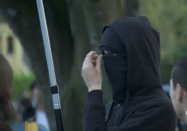 Masked thug carrying International Workers of the World flag at Grandview Park