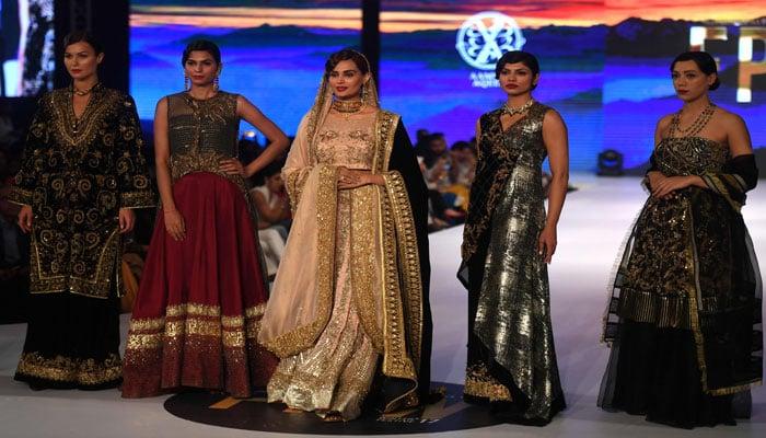 Models wear dresses designed by Models present creations by designer Aamna Aqeel. Photo: AFP