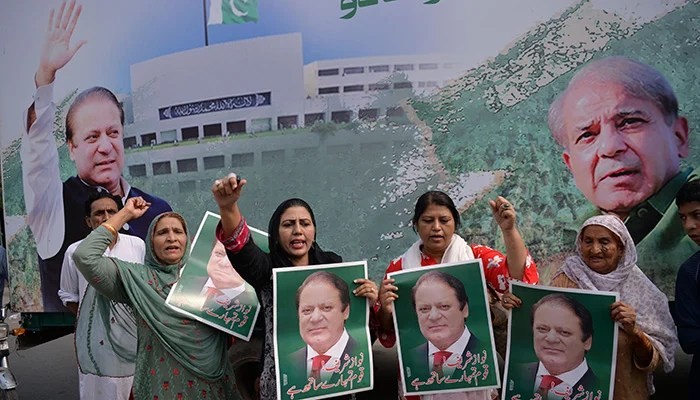 Supporters of former prime minister Nawaz Sharif hold posters of him and chant slogans as they gather at the venue where his younger brother Shehbaz Srarif will lead a rally towards the airport ahead of the arrival of Nawaz. Photo: AFP