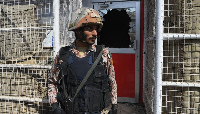 A Pakistani ranger stands in front of a damaged gate at the Chinese consulate after an attack in Karachi on November 23, 2018 - AFP