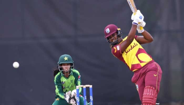 A West Indian bastman playing a shot while Pakistani wicketkeeper looks on.