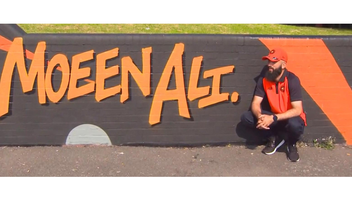 England cricketer Moeen Ali sitting beside his mural painted at Spark Green park in Birmingham. — Photo by author