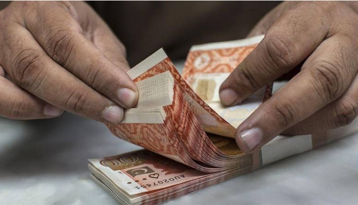 A currency dealer is counting Rs5,000 notes. — AFP/File