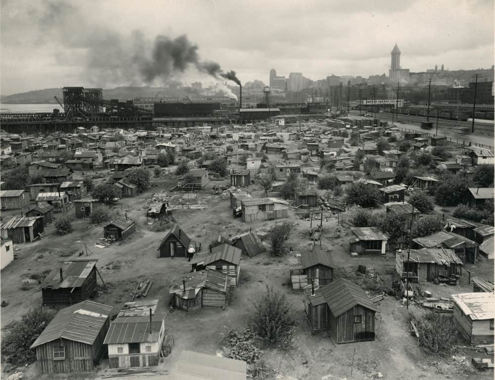 Hooverville was a homeless shantytown in Seattle Washington that remained in existed between 1931 to 1941. Photo: Hooverville water front and Connecticut , 1935, Warner, H.M. , State Library Photograph Collection, 1851-1990, Washington State Archives, Digital Archives, https://www.digitalarchives.wa.gov/record/view/b7a94a0dc95f7b3e0f1081fdb3a72c1e/, August 28, 2020.