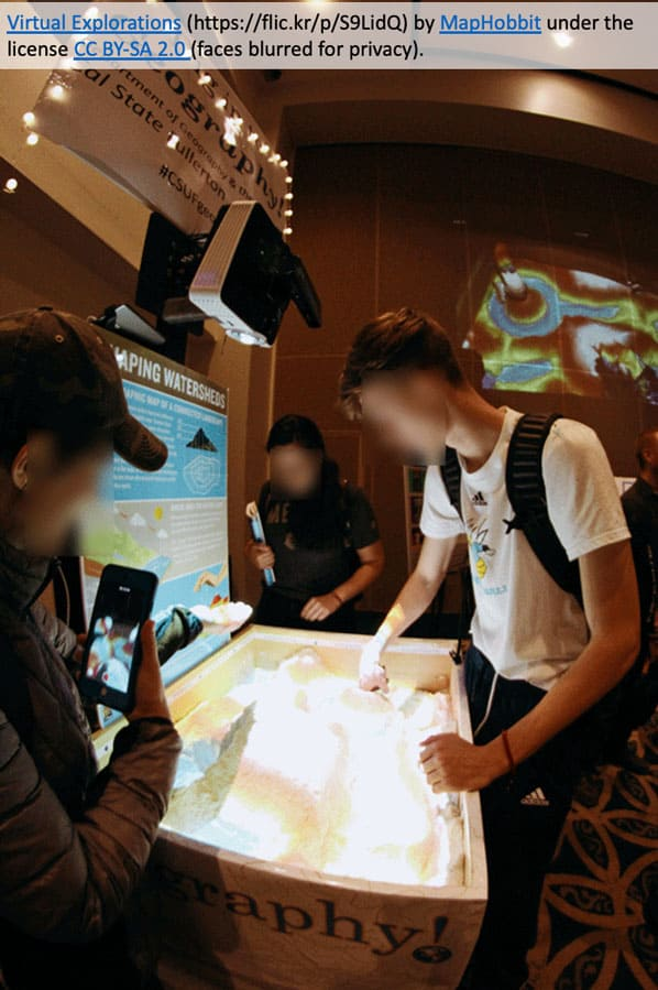 Virtual reality lets students explore topography and watersheds using an augmented reality sandbox provided by the Geography and the Environment Department, Cal State Fullerton. Photo: Virtual Explorations by MapHobbit under the license CC BY-SA 2.0 (faces blurred for privacy).