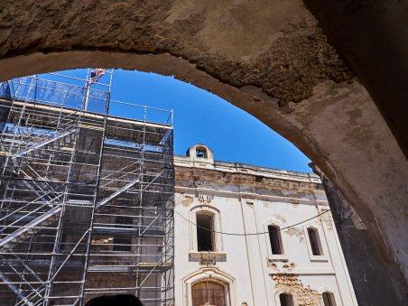 Los albañiles del SJNHS están removiendo el cemento usado en el pasado para reemplazarlo con una mezcla de cal y arena.