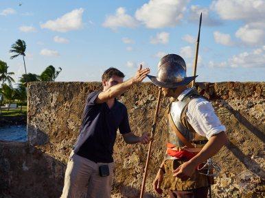 Manuel Manuel Minero (voluntario de los Amigos del Fortín San Jerónimo) y Félix E. Rivera (soldado siglo XVII) explican cómo la forma del morrión (casco de metal) ayuda a desviar un ataque con espada y protege la cabeza del soldado.