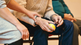 old man holding a yellow ball