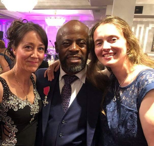 Debbie Kent and Tash Summerville with Rev. Bazil Meade, after being awarded MBE for contribution to Music