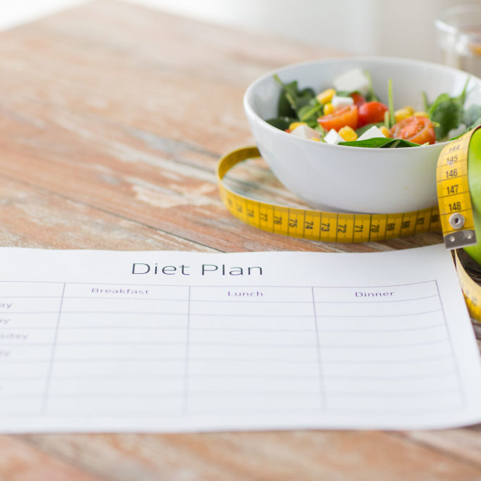 54304810 - healthy eating, dieting, slimming and weigh loss concept - close up of diet plan paper green apple, measuring tape and salad