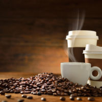 39336174 - cups of coffee with smoke and coffee beans on old wooden background