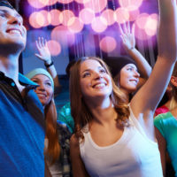 35024318 - party, holidays, celebration, nightlife and people concept - smiling friends waving hands at concert in club