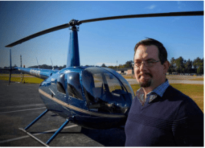 Man in his late 40's stands in front of helicopter.