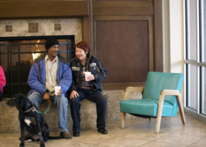 "Residents Ken Ellington, left, and Peggy Tidwell, right, talk with each other by the fireplace during ""Coffee Chat"" at the Palmer Court Apartments on Friday, Jan. 16, 2015, in Salt Lake City. The complex which provides housing for people who are chronically homeless encourages events like ""Coffee Chat"" to help build a community among the people who live there. ""This place is a blessing,"" says Tidwell who came to the facility after living under a tractor trailer for over four years. Photo by Kim Raff for NationSwell"