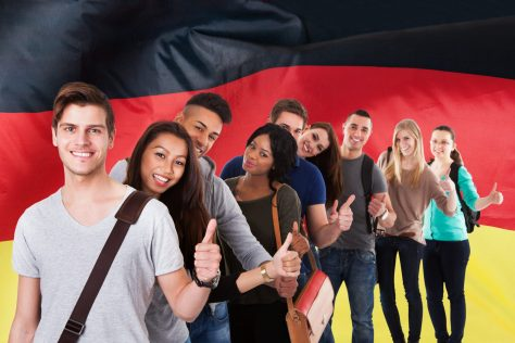 Multi Ethnic Students Standing In Front Of German Flag Showing Thumb Up