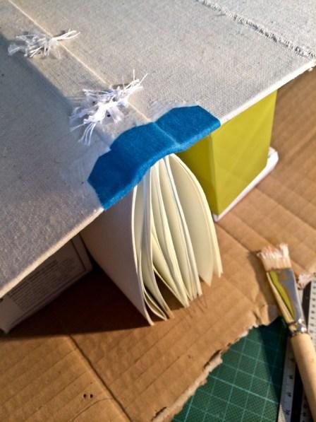 Die Hefte sind im Buchrücken eingenäht, die blaue Verzierung trocknet.
