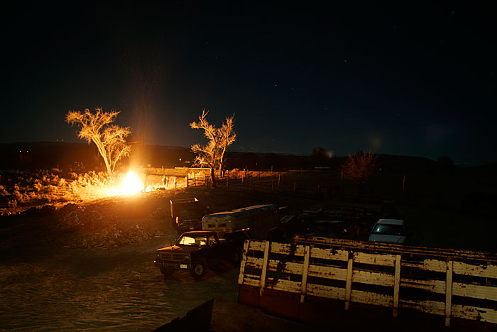 Canon EOS 1D MarkII — ISO 100 @ f/2.8 and 13sec — A bonfire lights up the surroundings in the Colorado desert.