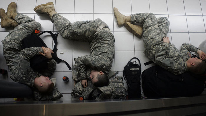 Soldiers take a nap Friday morning along the side of a stairwell at Lambert International Airport. Thousands of soldiers were at Lambert for the annual exodus home for the holidays from Fort Leonard Wood.