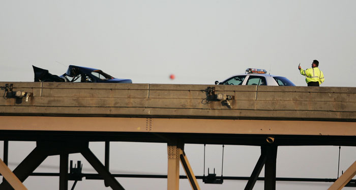 Friday, December 5, 2008 A police officer holds up his cell phone at the scene on an early-morning fatal accident that blocked all traffic on the Martin Luther King bridge.  Max Gersh | Post-Dispatch ©2008
