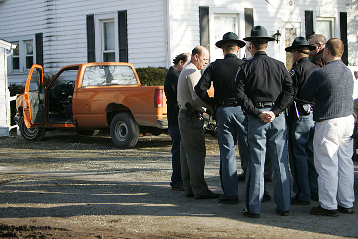 Officers from Henry and Randolph counties and state troopers stand in front of the house where two men were arrested Wednesday after a robbery. The truck in the background was allegedly the getaway vehicle. (C-T photo Max Gersh) ©2010
