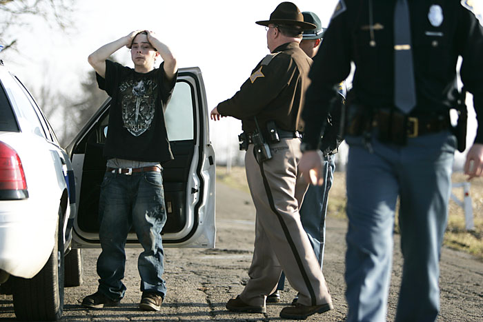 John Michael Evans places his hands on his head as Henry County Sheriff's deputies and Indiana State Troopers transfer him into the custody of the Randolph County Sheriff's Department. Evans was caught at his residence after allegedly committing armed robbery in Losantville. (C-T photo Max Gersh) ©2010