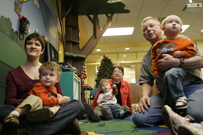 Jennifer Hood, left, holds Ezra, one of her 2-year-old twins, while the other, Eli, sits in the lap of Hood's mother, Jan Masengale, center. Also pictured is Gerald Darling holding his 2-year-old grandson, Jacob Specht. The children were attending a toddler story time session on April 8, at the New Castle-Henry County Public Library. (C-T photo Max Gersh)