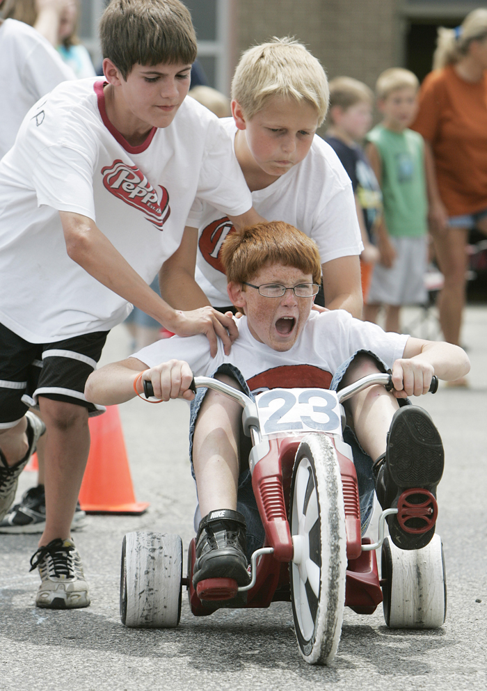 In this Wednesday May 26, 2010 photo, Jordan Rhodus lets out a  scream as teammates Grant Jessup, left, and Travis Isaacs give him a  push start out of the pit during the Titan 500 at Tri Elementary Schoo  in Straughn, Ind. Their team, No. 23 Dr. Pepper, went on to win the  race. (AP Photo/The Courier-Times, Max Gersh) ©2010