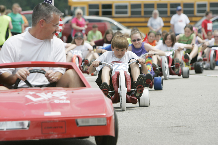 In this May 26, 2010 photo, Corbin Pew,  number 23, leads the pack of Big Wheel tricycle racers behind pace car driver Ken Gregory Wednesday afternoon during a warm up lap at the Titan 500 in Straughn, Ind. This is Pew's third year racing. (AP Photo/The Courier-Times, Max Gersh) ©2010