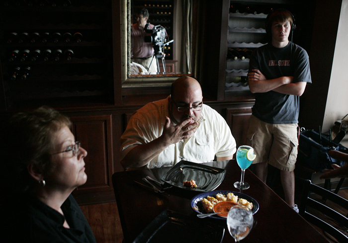 "Dean Wilson, host of ""Savor Indiana,"" licks his fingers after tasting Durham's crab bread Tuesday afternoon. Rosie Shank, left,  Durham's kitchen manager, talks with cameraman Greg Williams, seen in the mirror. Also pictured is Keith Jackson, production assistant at right. (C-T photo Max Gersh) ©2010"