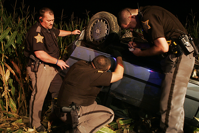 Henry County Sheriff Deputies take down the VIN number off of a 1987 Mercedes Benz late Wednesday night after it wrecked in a cornfield near the intersection of Road 300S and Ind. 103. (C-T photo Max Gersh) ©2010