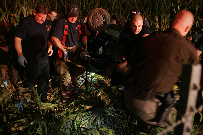 Emergency respodners carry Jimmy Luna, 17, New Castle, from a mangled vehicle to a waiting ambulance Wednesday night near the intersection of Road 300S and Ind. 103. (C-T photo Max Gersh) ©2010