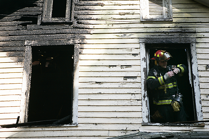 A firefighter communicates out of a second story window with crews on the ground Thursday afternoon while trying to locate hot spots in a home in Spiceland. (C-T photo Max Gersh) ©2010