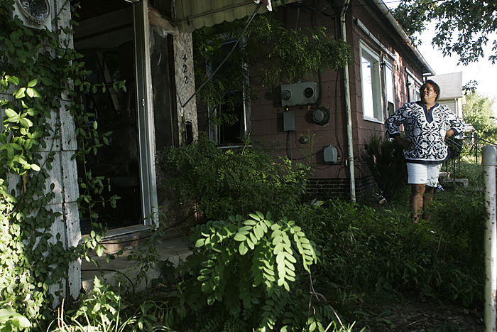 Lisa Archey stands in between two abandoned and neglected homes on August 25 along North 17th Street. Archey said that having homes like these on the block hurt the entire community. (C-T photo Max Gersh) ©2010