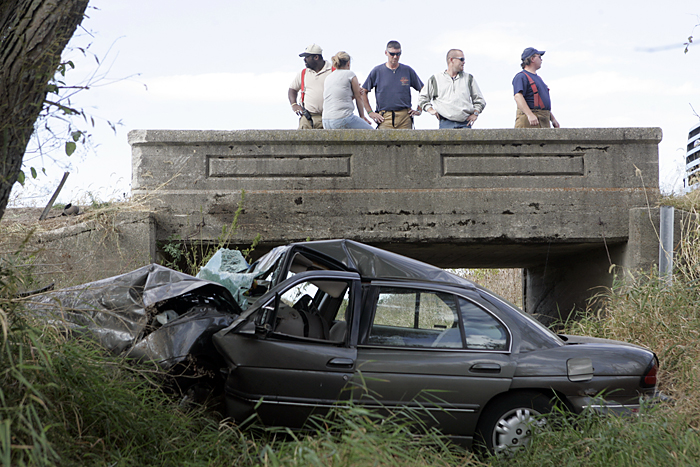 Emergency responders stand on an overpass along County Road 500S Thursday afternoon after a vehicle occupied by two 16-year-old girls left the roadway and landed in a small creek bed. (C-T photo Max Gersh) ©2010