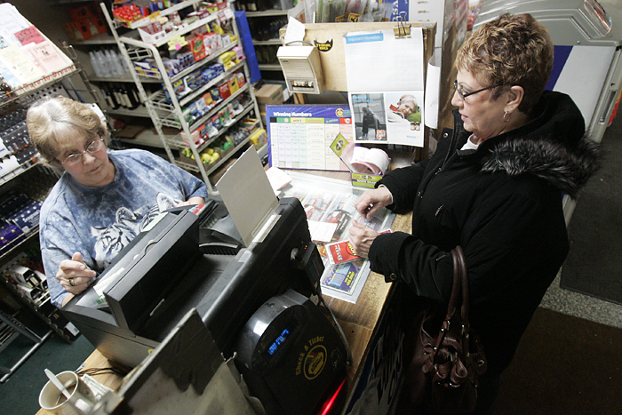 "MAX GERSH | ROCKFORD REGISTER STAR ©2011 Barbara Kirchner (left) checks Angie Jackson's lottery tickets Thursday, Jan. 6, 2011, at Central Park Tap in Rockford. Jackson has been buying lottery tickets there twice a week for about 15 years, playing the same numbers every time. She won $150 on her Mega Millions ticket. ""You can't win if you don't play,"" Jackson said."