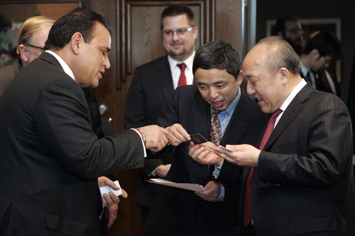 MAX GERSH | ROCKFORD REGISTER STAR Dr. Lu Guanqiu, founder and chairman of Wanxiang, (from right) and Pin Ni, president of Wanxiang America Corporation, look at Sunil Puri's business card Thursday, Jan. 20, 2011, at Giovanni's Restaurant and Convention Center in Rockford.