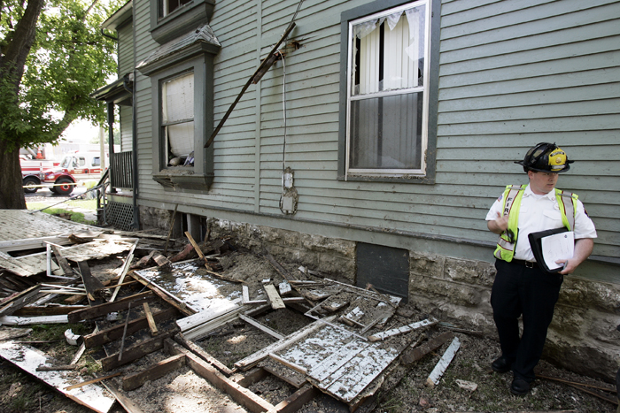MAX GERSH | ROCKFORD REGISTER STAR Rockford Fire Investigator Tim Morris stands in between a home that exploded and the home  to its south Friday, May 20, 2011, in the 400 block of Kishwaukee Street in Rockford. The neighboring home has been condemned from extensive damage and debris caused by the explosion. ©2011