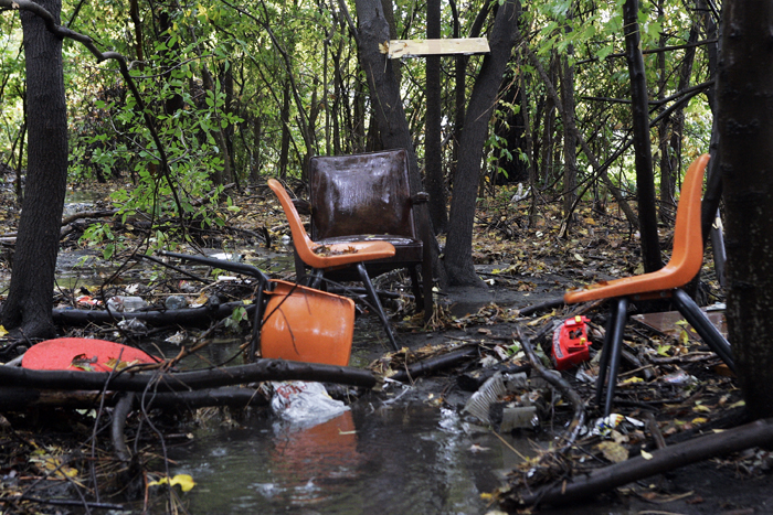 MAX GERSH | ROCKFORD REGISTER STAR Chairs and other garbage sit in the woods between the old Rock River School and Kishwaukee Street Thursday, Oct. 13, 2011, in Rockford. © 2011
