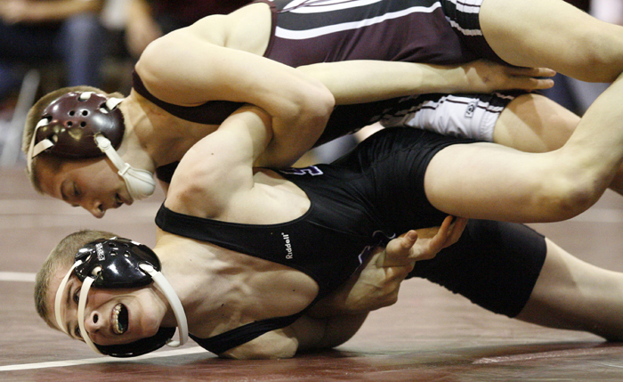 Dakota's Dillon Swift (top) works to get Lutheran's Austin Grant on his back in the 106-pound championship bout Saturday, Feb. 2, 2013, during the Class 1A wrestling regional at Dakota High School. Swift went on to win the bout. MAX GERSH/ROCKFORD REGISTER STAR ©2013