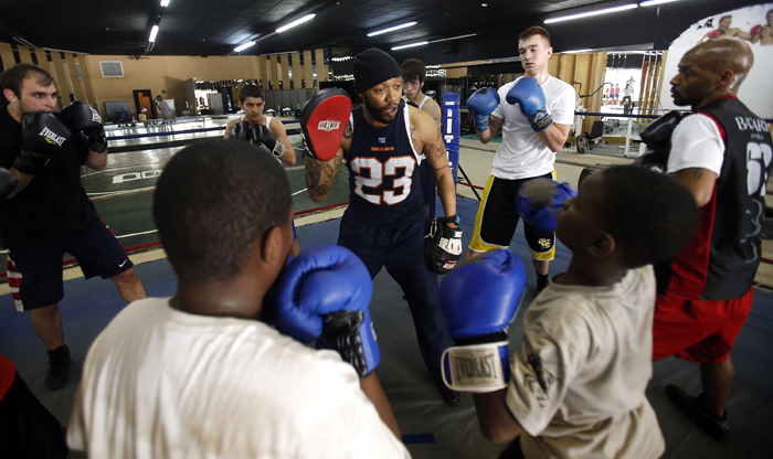 Tony Bandy (center) holds up a target as he is surrounded by boxing students Tuesday, April 30, 2013, at Fight College on North Main Street in Rockford. MAX GERSH/ROCKFORD REGISTER STAR ©2013