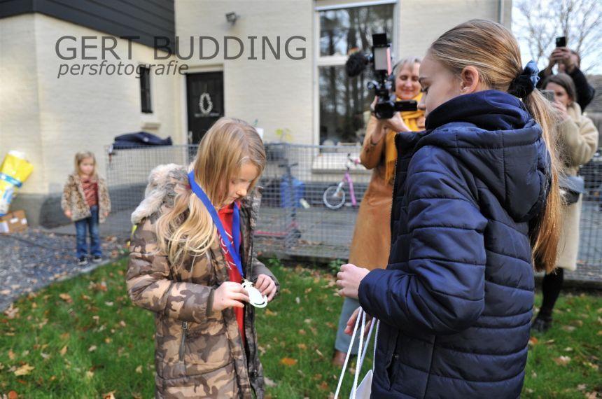 Kinderburgemeester Julot Hulsebos geeft aan Valerie, Remi en Marith een kinderlintje