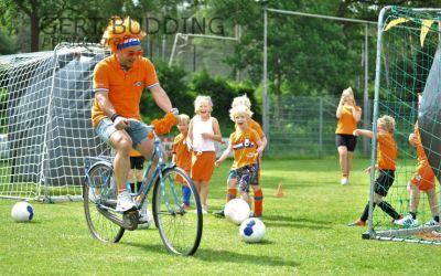 Oranje gekleurde jeugd RVW knalt er vrolijk op los. 'Leeuw' mocht van de fiets worden geschoten