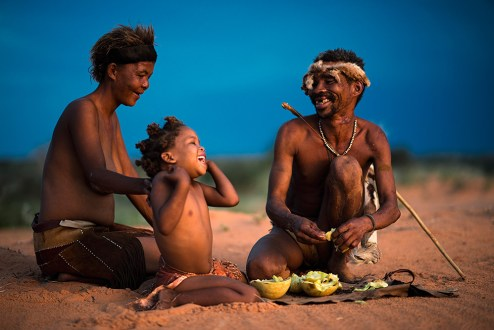 I met this family of Bushmen from the Kruiper family in the Kalahari. They had tsammas with them, which they ate while I took the photos. This photo was taken at sunset with the last rays of the sun casting a soft glow of light onto them. - By Ferdinand Veer, Kalahari Nikon D800E, Nikkor 85mm f/1.4, ISO 100, f/1.4, 1/100 sec