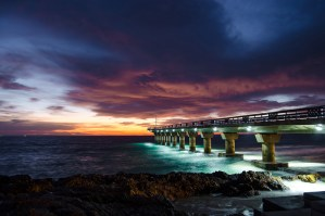It was a cloudy morning and although I was not sure if I would get a good sunrise, I decided to head out to Shark Rock Pier at Hobie Beach in Port Elizabeth. Upon arrival the colour of the clouds was magnificent. I set up my camera and captured this shot. There was no wind, and the reflection of the lights and colours on the ocean was absolutely beautiful. - By Cindy Bester, Despatch Nikon D5100, Nikkor 18-55mm f/3.5-5.6, ISO 100, f/4,5, 2.5 sec