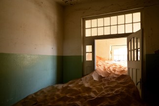 A derelict room located in Kolmanskop, Luderitz. This abandoned hospital is rundown now, filled only with desert sand. - Kayleigh-Anne Brogan, Cape Town, Nikon D610, Nikkor 24-85mm f/3.5-4.5G ED VR, ISO 640, f/4, 1/80 sec