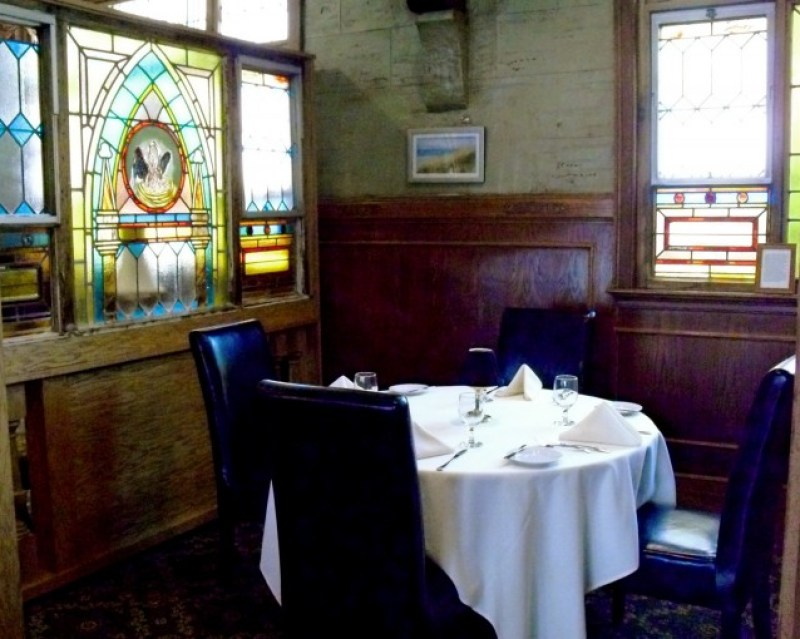 upscale dining linen table-set nook with Church-style stained glass. Belfry Inne Bistro, Sandwich MA