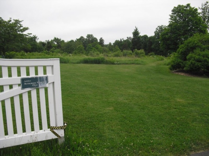 Picket fence opens onto pastoral green field at Greenwich CT Audubon Center
