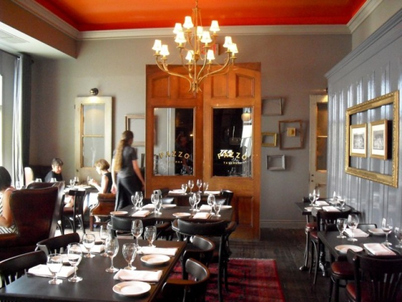 Interior of upscale restaurant with candle-lamp chandelier and mirror armoire